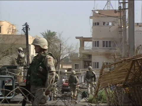 US military policewoman on guard by barbed wire on street with bomb wreckage in background/ Baghdad Iraq
