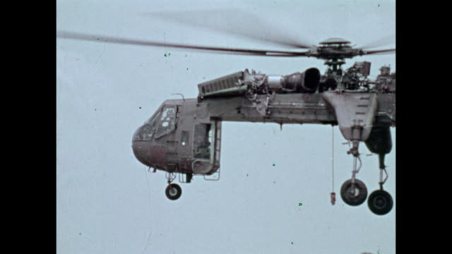 / military recruitment film man climbs onto sky crane support helicopter inspects it the helicopter picks up truck / montage of helicopters flying