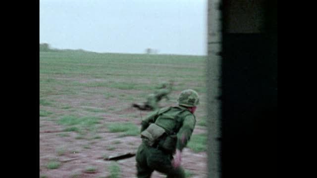 / military recruitment film military exercise helicopter formation carrying airmobile troops lands and they run out / soldiers rappel to the ground...