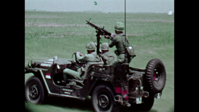 / military recruitment film military exercise involving troops on helicopters jeep carrying an M2 machine gun tanks and artillery