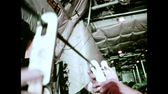 / military recruitment film paratroopers ready themselves inside the body of a C130 Hercules transport plane / green light signal turns on troops...