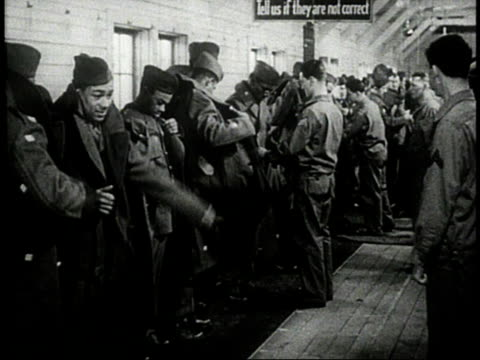 military recruits shrugging into trench coats / Men buttoning their coats then saluting each other