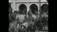 LS military supply wagons proceed down a boulevard with arched towers / former Crown Prince Wilhelm stands with German officers / soldiers with...