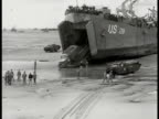 Military truck driving out of US LSM 281 landing transport ship docked beachfront Armored car driving out of same transport ship TU WS US Soldiers...