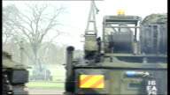 Military vehicles along through army base ENGLAND Hampshire Aldershot EXT Tanks along with soldiers inside / military vehicles along through grounds...