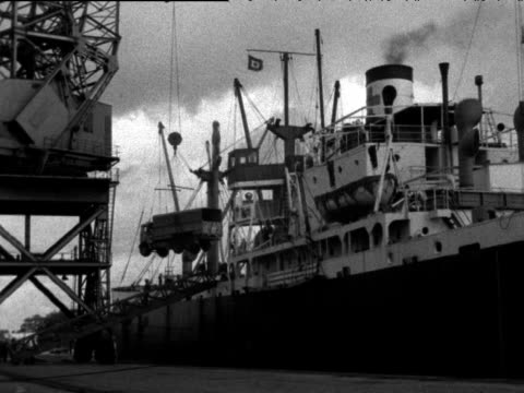 Military vehicles being loaded by crane onto ship for transit to Egypt Suez Crisis Southampton 26 Aug 56