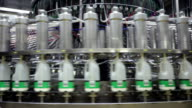 Milk bottles being filled with milk by a large spiraling machine