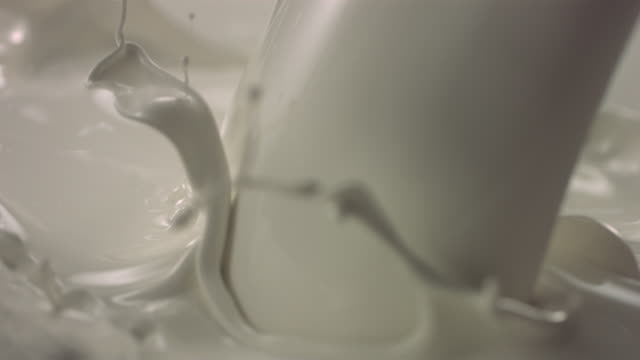 CU SLO MO Milk pouring and splashing