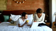 Millennial Multi Ethnic Couple in Bed with Laptop and Coffee