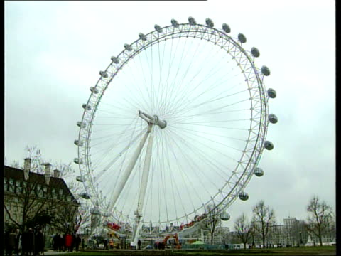 Millennium wheel opens a month late ITN London Embankment Millennium Wheel with laser beams shining on it LA MS Laser highlighted pod TILT DOWN...