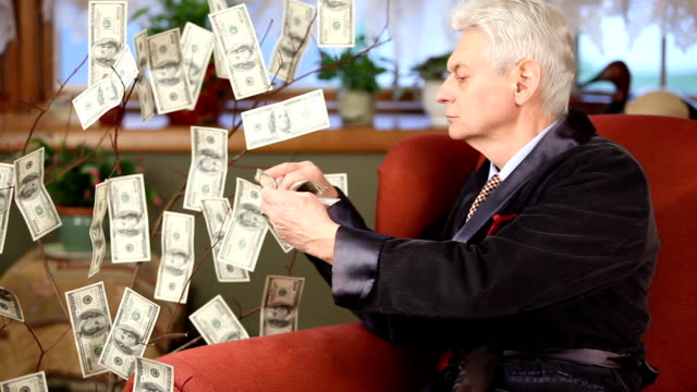 Millionaire in armchair picking 100 dollar bills off Money Tree