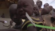 Millions at risk of famine as drought continues and government spends money on arms SOUTH SUDAN Kapoeta INT Child suspended in sling as being weighed...