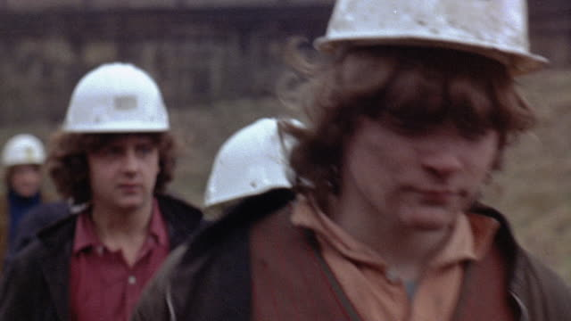 1971 MONTAGE Miner apprentices watching film on safety and miners walking outside the plant / United Kingdom