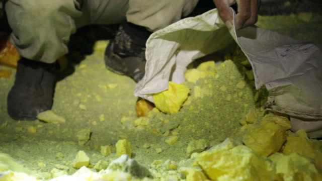 MS Miner collecting solid sulfur from inside the volcano at night / Ijen, Java, Indonesia