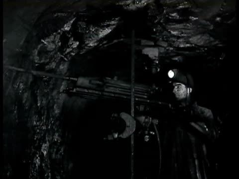 Miner drilling in mine wall CU Water cooled drill bit drilling into mine wall WWII