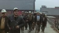 1971 MONTAGE Miners walking across bridge outside mine / United Kingdom