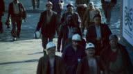 TD Miners walking on sidewalk below shaft tower / Yorkshire, England, United Kingdom