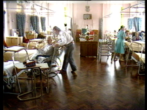 Minimum wage ENGLAND Hastings GV Hospital ward as orderly pushes elderly man in wheelchair Camberwell MS Cleaner polishing floor MS Woman working in...