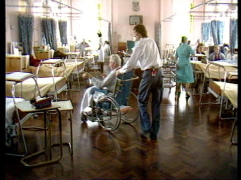 Hastings GV Hospital ward as orderly pushes elderly man in wheelchair R