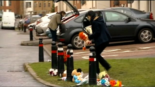 body found / neighbours attend church service Edinburgh Ferry Gait Crescent Woman laying flowers amongst other floral tributes on ground outside...