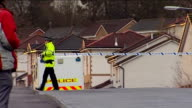 body found / neighbours attend church service Police officer putting cordon tape across road outside bungalow GV Cordonned off area of woodland the...