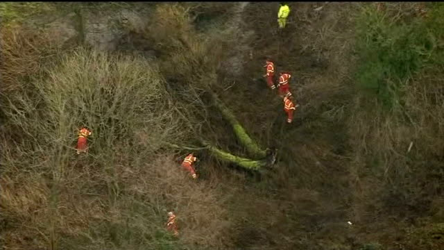 body found / neighbours attend church service EXT Search team searching woodland
