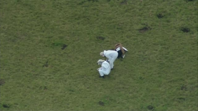 man arrested on suspicion of murder AIR VIEW / AERIAL forensic police officers in field