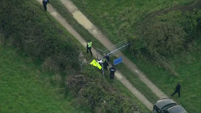 man arrested on suspicion of murder Dorset VIEWs / AERIALs police officers searching field