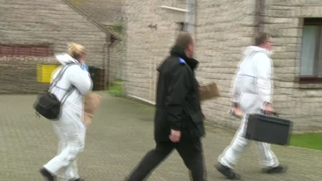 man arrested on suspicion of murder Dorset EXT Police forensic officers along towards house entrance