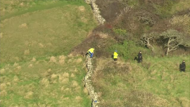 Third suspect released / police search widened Dorset Swanage VIEWs / AERIALs police officers searching cliff top fields and bushes
