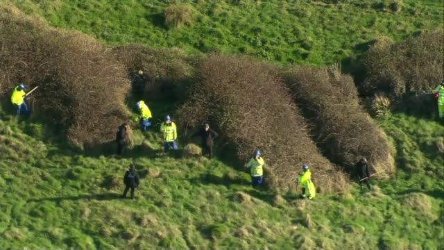 Third suspect released / police search widened ENGLAND Dorset Swanage VIEWs / AERIALs police officers searching cliff top fields and bushes / police...