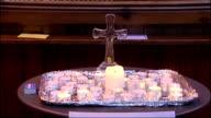 police search / church vigil / rescue team INT **Choir music heard SOT** Lit candle as church music heard in background / Various shots candles...