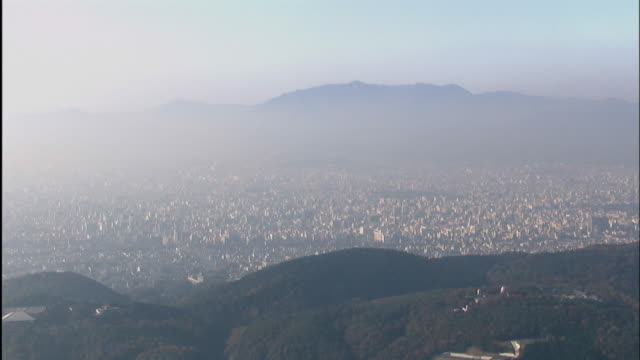 A mist drifts above Kyoto in the vast basin.