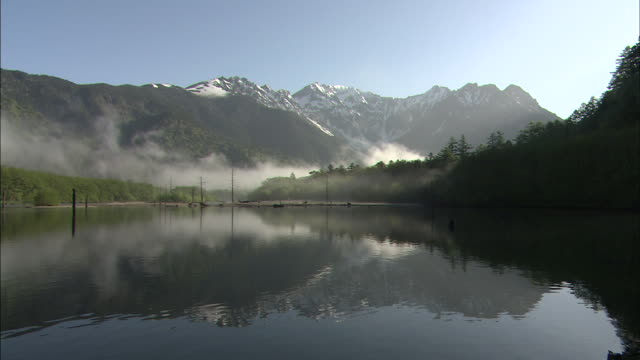 Mist settles across the foothills of the Hodaka Range in Nagano, Japan.