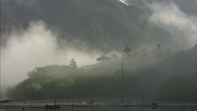 Mist settles over a mountain lake in the foothills of the Hodaka Range in Nagano, Japan.