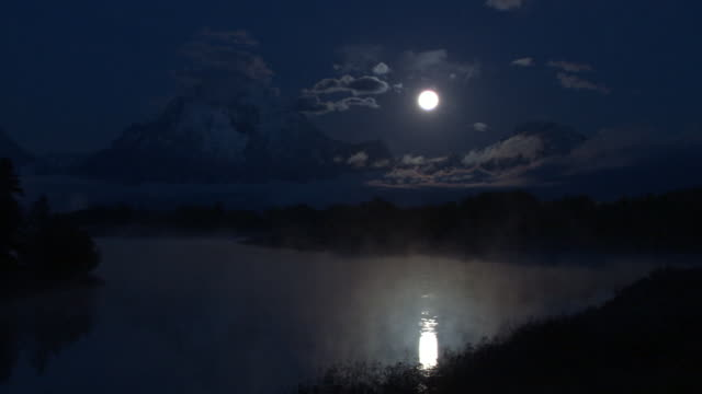 Mist swirls over moonlit lake at night, Yellowstone, USA