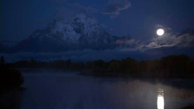 Mist swirls over moonlit mountain lake at night, Yellowstone, USA