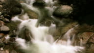 Misty water slowly flows over river rocks.