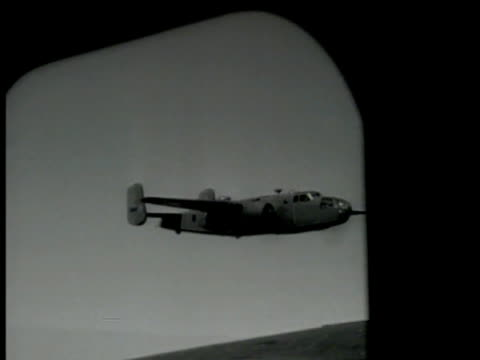 B25 'Mitchell' Bomber in flight TD WS Black smoke fire in unidentified bombed target area near port WWII