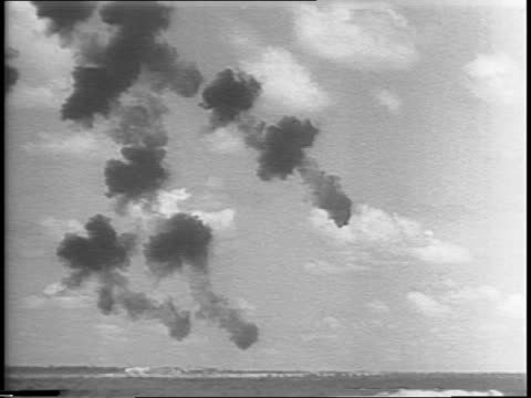 Mitchell bombers drop phosphorous bombs / antipersonnel bombs explode into fragments just above ground / two B25s drop belly tank bombs / huge...