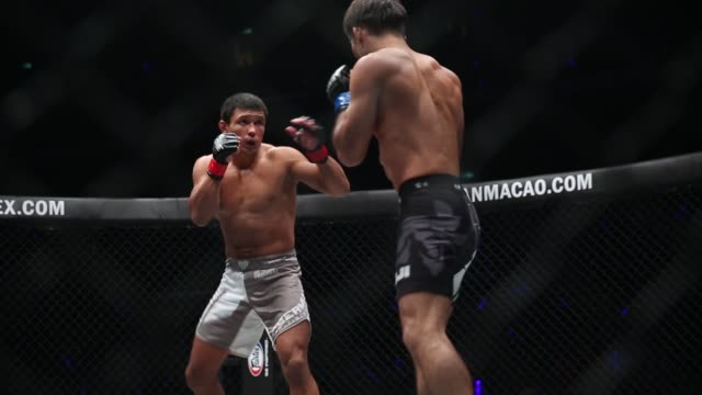 Mixed martial arts fighters Timofey Nastyukhin in white shorts and Koji Ando contest a lightweight bout at The One Kings Conquerors event at the...
