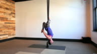 Mixed Race aerial yoga instructor working out on silks