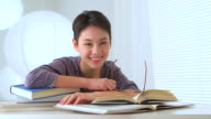Mixed race Asian woman with a pile of books