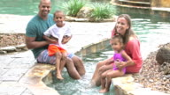 Mixed race family of four at tropical swimming pool