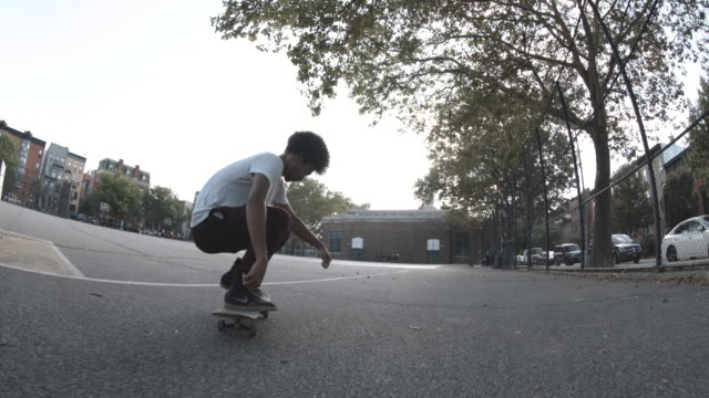 A mixed race man skateboards in the streets of Brooklyn during the summer of 2017.