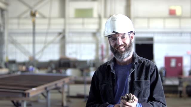 Mischlinge-Mann arbeitet in Fabrik, geht bis zu Kamera