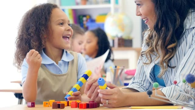 Mixed race preschool student enjoys playing with counting blocks