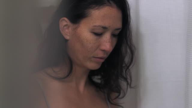 Mixed race woman washing face in bathroom mirror