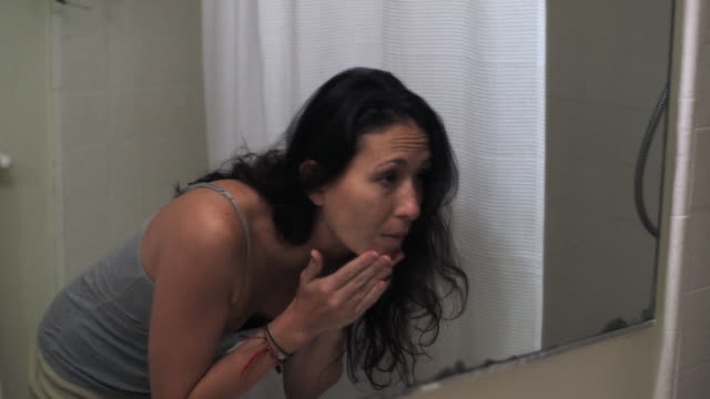 Mixed race woman washing face in bathroom mirror
