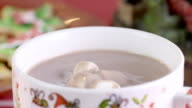 MMarshmallows falling on hot chocolate mug in slow motion